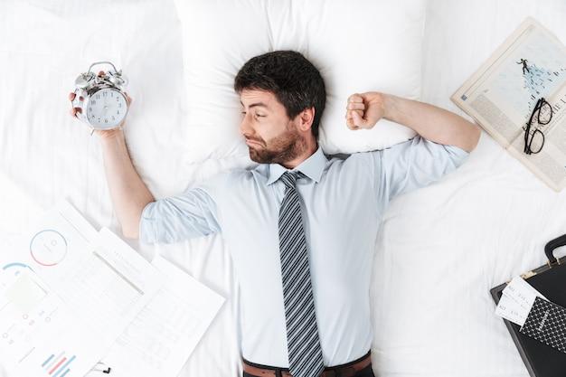 Przystojny młody biznesmen rano w łóżku leży śpiąca trzymając budzik