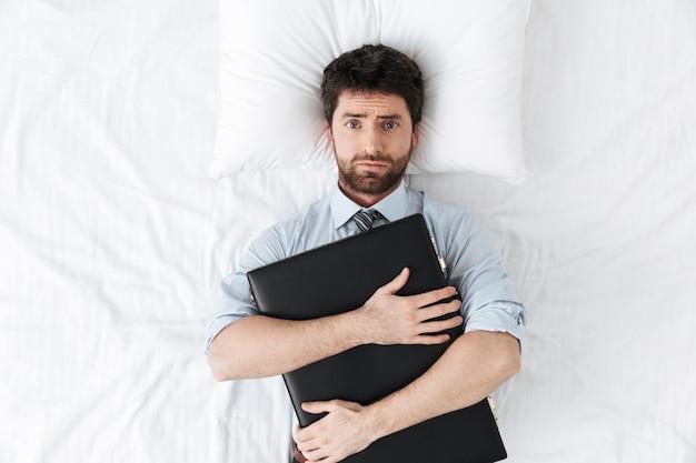 Przystojny młody biznesmen rano w łóżku leży trzymając torbę