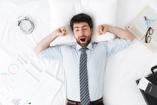 Przystojny młody biznesmen rano w łóżku leży ziewanie