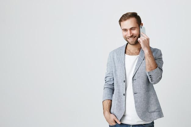 Przystojny młody biznesmen rozmawia przez telefon komórkowy