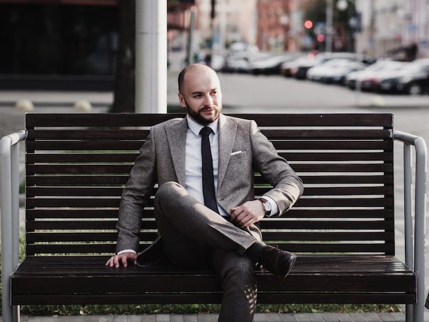 Przystojny młody biznesmen siedzi na ulicy