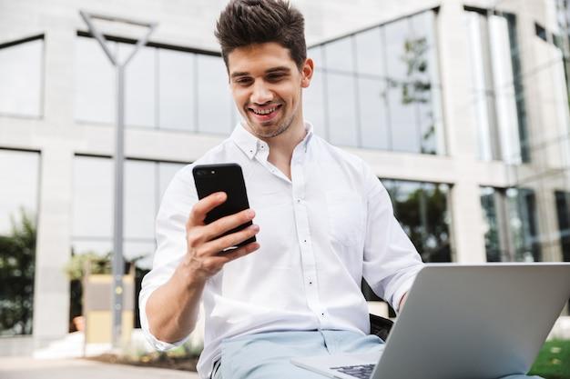 Przystojny młody biznesmen siedzi na zewnątrz przy użyciu komputera przenośnego i telefonu komórkowego