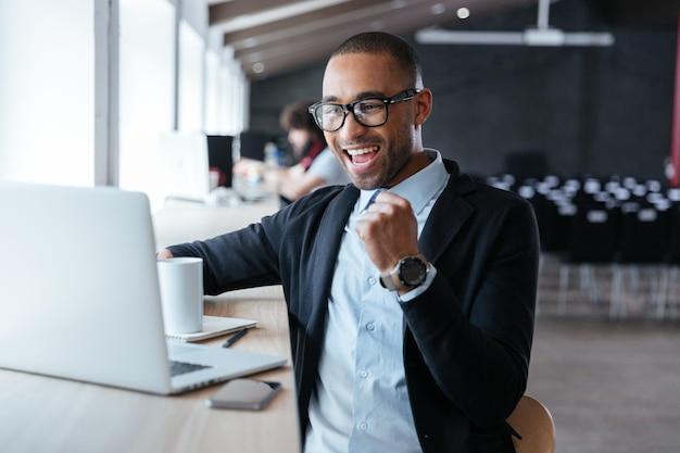 Przystojny młody biznesmen siedzi przy swoim biurku, świętując sukces z podniesionymi rękami, patrząc na ekran swojego laptopa