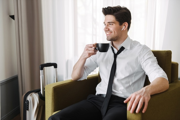 Przystojny młody biznesmen siedzi w fotelu w hotelu z walizką, po filiżance kawy