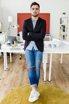 Przystojny młody biznesmen spojrzenie na aparat fotograficzny w biurze.