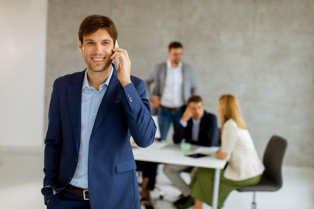 Przystojny młody biznesmen stoi pewnie w biurze przed swoim zespołem i przy użyciu telefonu komórkowego