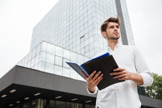 Przystojny młody biznesmen stojący i trzymający dokumenty w folderze na zewnątrz
