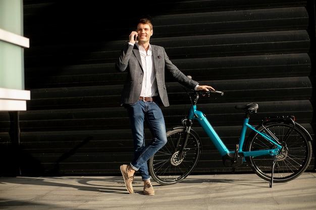 Przystojny młody biznesmen stojący przy ebike i za pomocą telefonu komórkowego