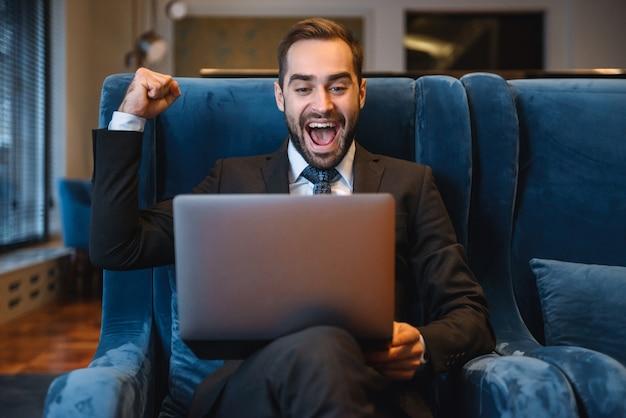Przystojny młody biznesmen ubrany w garnitur siedzi w holu hotelu, przy użyciu komputera przenośnego, obchodzi