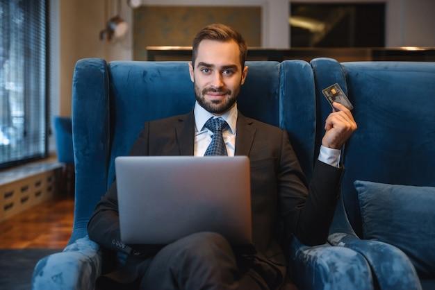 Przystojny młody biznesmen ubrany w garnitur siedzi w holu hotelu, przy użyciu komputera przenośnego, pokazując plastikową kartę kredytową