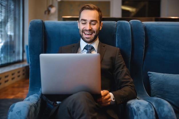 Przystojny młody biznesmen ubrany w garnitur siedzi w holu hotelu przy użyciu komputera przenośnego