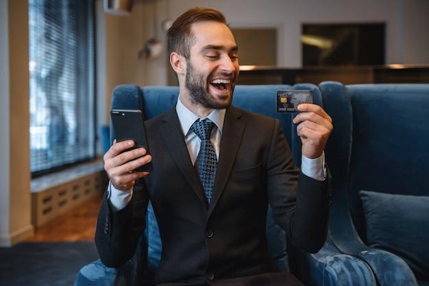 Przystojny młody biznesmen ubrany w garnitur siedzi w holu hotelu, przy użyciu telefonu komórkowego, pokazując plastikową kartę kredytową