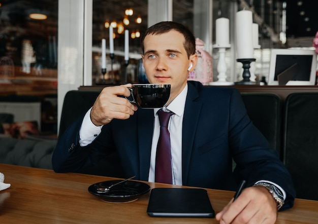 Przystojny młody biznesmen uśmiecha się i pije kawę w kawiarni. mężczyzna w garniturze z kawą.