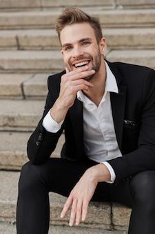 Przystojny młody biznesmen uśmiechający się siedzący na schodach na ulicy miasta, ubrany w garnitur