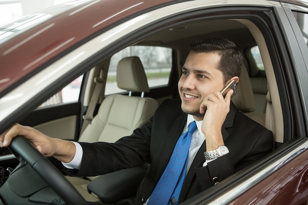 Przystojny młody biznesmen używa jego telefonu obsiadanie w samochodzie