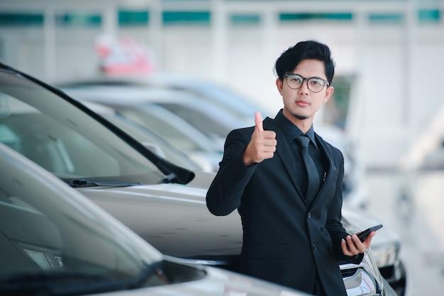 Przystojny młody biznesmen w azji pokaż radość z ukończenia sprzedaży nowego salonu samochodowego.