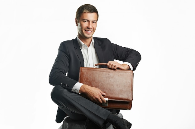 Przystojny młody biznesmen w czarnym garniturze trzyma walizkę