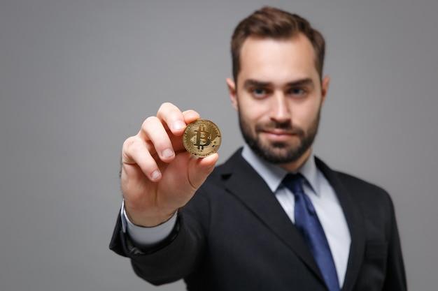 Przystojny młody biznesmen w klasyczny czarny garnitur koszula krawat pozowanie na białym tle na szarej ścianie. osiągnięcie koncepcji biznesowej bogactwa kariery. trzymanie bitcoina, przyszłej waluty.