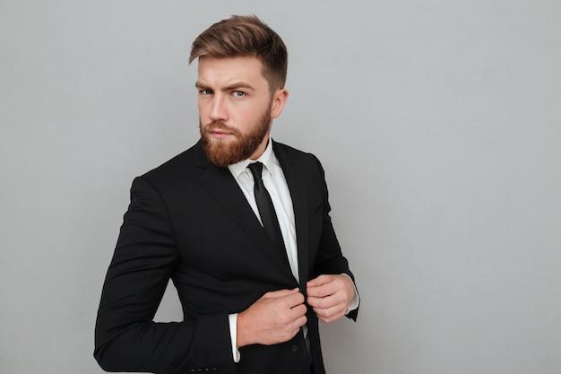 Przystojny młody biznesmen w kostium pozyci