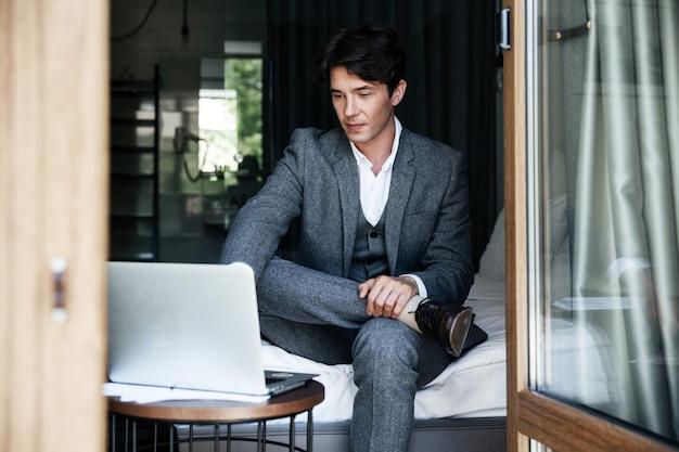 Przystojny młody biznesmen w kostiumu pracuje na laptopie