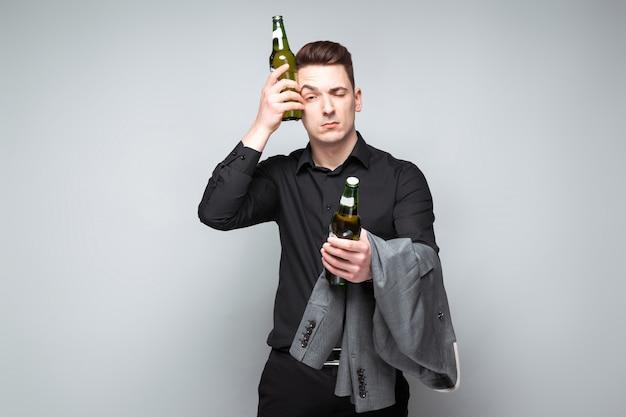 Przystojny młody biznesmen w kosztownym zegarku i czarnej koszuli posiada szarą kurtkę i piwo