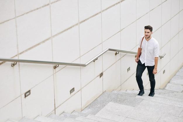 Przystojny młody biznesmen z torbą chodzący po schodach