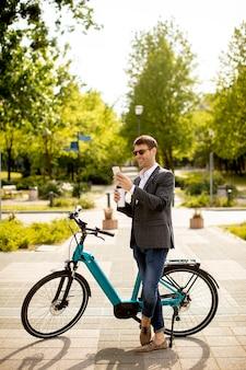Przystojny młody biznesmen za pomocą telefonu komórkowego przez ebike z filiżanką kawy na wynos