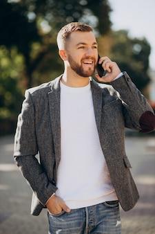 Przystojny młody biznesmen za pomocą telefonu poza ulicą