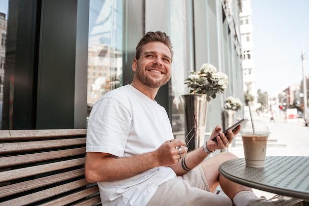 Przystojny młody blondyn siedzi na tarasie kawiarni z kawą napój uśmiechający się z mobilnego smartfona na tle odbicia budynku ulicy szkła wielkiego miasta. tysiącletni hipster w słoneczny letni dzień