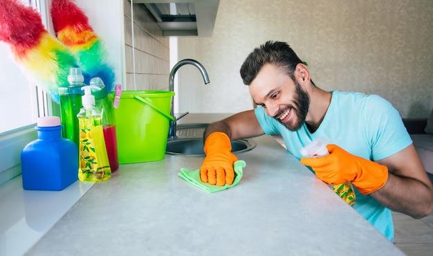 Przystojny młody brodacz w t-shirt wyciera stół specjalnymi narzędziami w kuchni podczas sprzątania domu