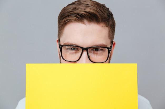 Przystojny młody brodaty biznesmen trzyma pustego papier