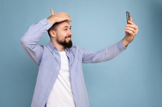 Przystojny młody brodaty brunet ubrany w stylowe ubrania na białym tle nad niebieską ścianą trzymając smartfon przy selfie zdjęcie patrząc na ekran telefonu komórkowego.