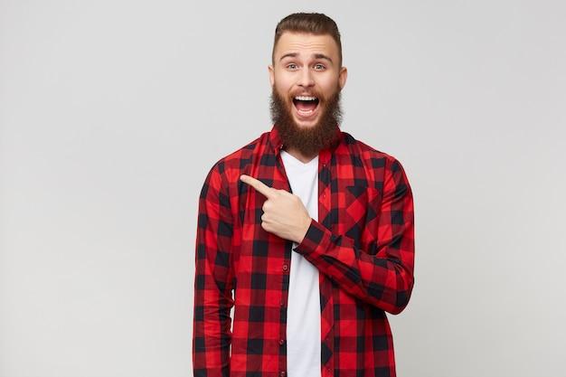 Przystojny młody brodaty facet w kraciastej koszuli z wąsami fryzury moda. nie wierzy w swoje szczęście, otworzył usta ze zdumienia wskazując palcem w lewo, na białą ścianę