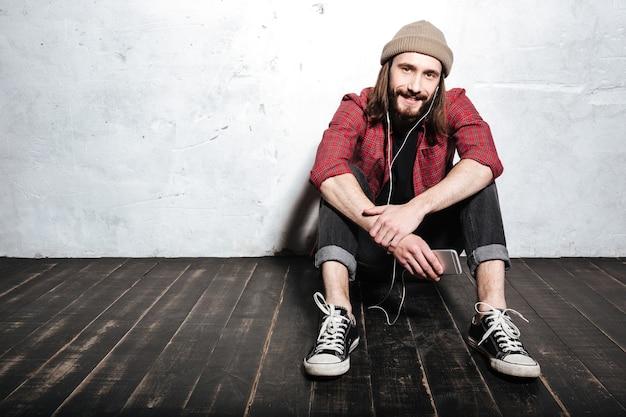 Przystojny młody brodaty hipster mężczyzna w kapeluszu ubrany w koszulę w klatce, siedzący na podłodze odizolowanej nad ścianą podczas słuchania muzyki przez słuchawki