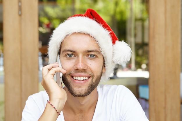 Przystojny młody brodaty hipster w czerwonym kapeluszu z białym futrem pozuje w pomieszczeniu jak święty mikołaj, po miłej rozmowie telefonicznej
