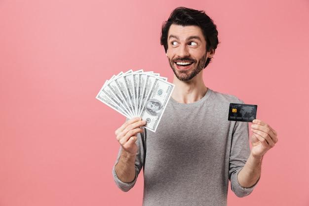 Przystojny młody brodaty mężczyzna brunetka ubrana w sweter stojący na różowo, pokazując kartę kredytową, trzymając banknoty pieniędzy