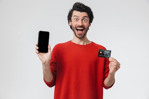 Przystojny młody brodaty mężczyzna brunetka ubrany w sweter stojący na białym, pokazując pusty ekran telefonu komórkowego i karty kredytowej
