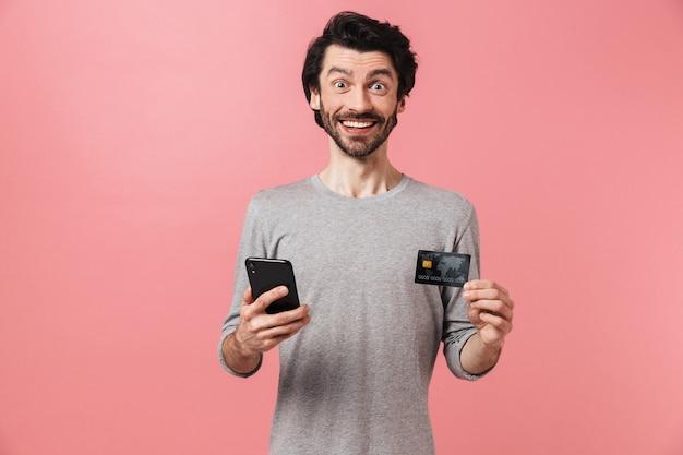 Przystojny młody brodaty mężczyzna brunetka ubrany w sweter stojący na różowo, pokazując pusty ekran telefonu komórkowego i karty kredytowej