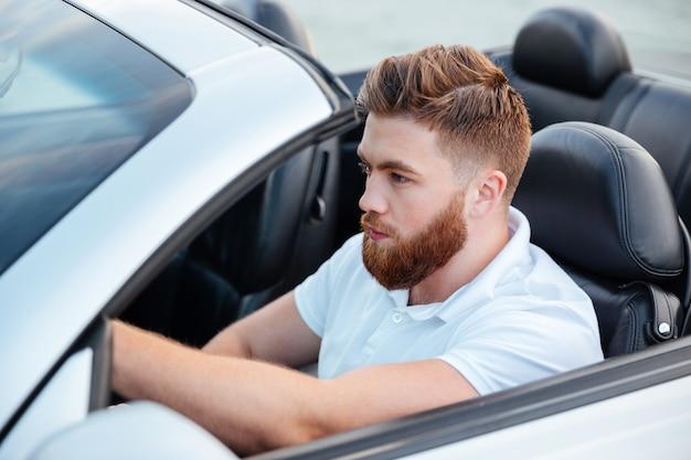 Przystojny młody brodaty mężczyzna jedzie jego samochód kabriolet