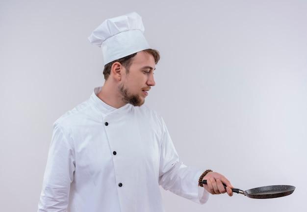 Przystojny młody brodaty mężczyzna kucharz na sobie biały mundur kuchenki i kapelusz patrząc na patelnię na białej ścianie