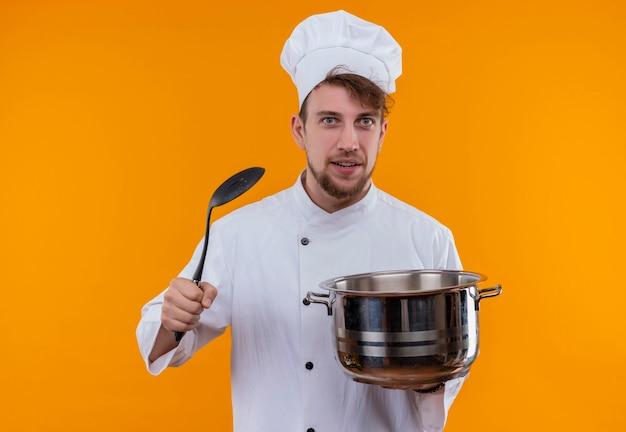 Przystojny młody brodaty mężczyzna kucharz w białym mundurze, trzymając patelnię do sosu z łyżką cedzakową, patrząc na pomarańczową ścianę