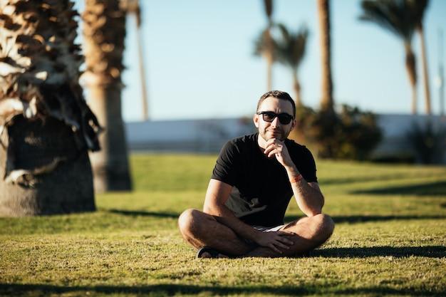 Przystojny młody brodaty mężczyzna patrząc na bok w okularach przeciwsłonecznych, siedząc na trawie pod palmami na wakacjach.