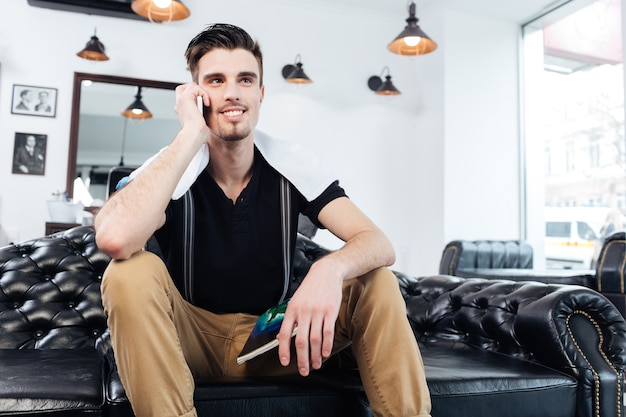 Przystojny młody brodaty mężczyzna rozmawia przez telefon komórkowy, siedząc na kanapie w salonie fryzjerskim
