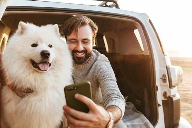 Przystojny młody brodaty mężczyzna siedzący z tyłu samochodu, bawiący się z psem na plaży, robiący selfie
