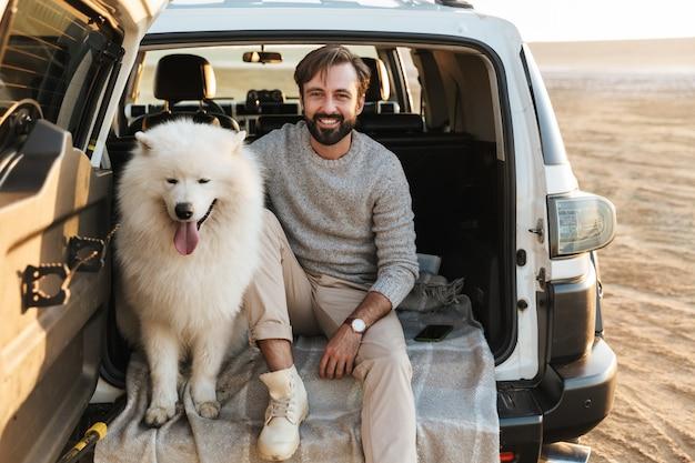 Przystojny młody brodaty mężczyzna siedzący z tyłu samochodu, bawiący się z psem na plaży