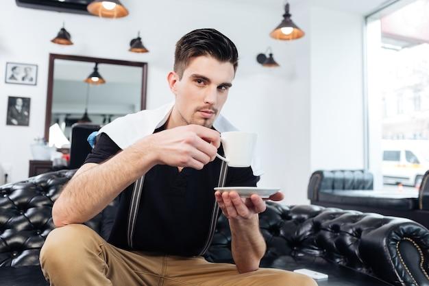 Przystojny młody brodaty mężczyzna trzyma filiżankę kawy i siedzi na kanapie u fryzjera