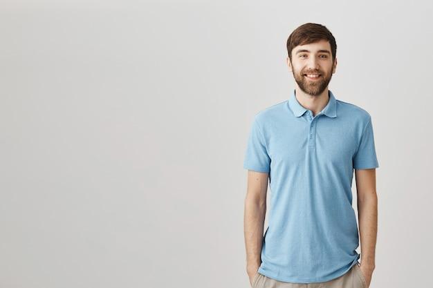 Przystojny młody brodaty mężczyzna uśmiecha się i wygląda szczęśliwy