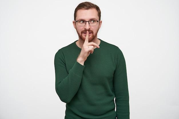 Przystojny młody brodaty mężczyzna w okularach z brązowymi krótkimi włosami trzymający palec wskazujący na ustach i patrząc na bok, prosząc o zachowanie tajemnicy, odizolowany