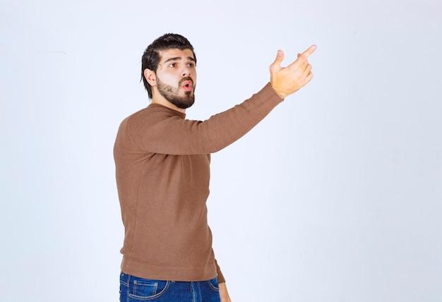 Przystojny młody brodaty mężczyzna, wskazując na szarym białym tle. zdjęcie wysokiej jakości