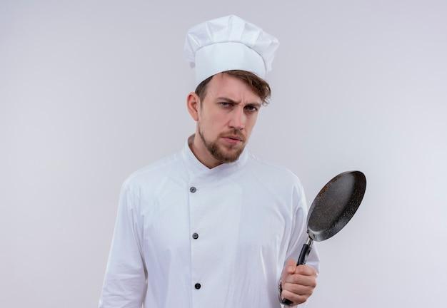 Przystojny młody brodaty szef kuchni ubrany w biały mundur kuchenki i kapelusz trzymający patelnię, patrząc z agresywnym wyrazem twarzy na białej ścianie